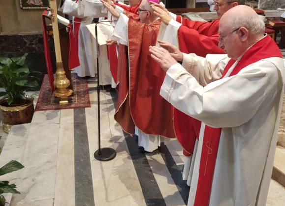 Vescovo e preti impongono le mani per la Cresima